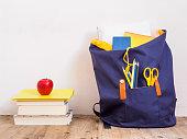 Blauer Schulrucksack mit Schreibartikeln, einen Bücherstapel und einem roten Apfel auf einem braunen Holzfußboden. Schule, Bildung, Wissen.
