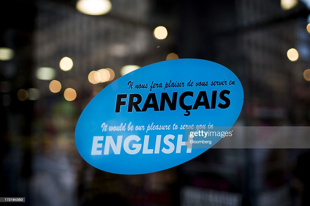 A bilingual sign hangs outside a shop in Montreal, Quebec, Canada, on Monday, July 8, 2013. Montreals city council elected Laurent Blanchard as interim mayor to replace Michael Applebaum, who quit last week after being arrested on corruption charges. Photographer: Brent Lewin/Bloomberg via Getty Images
