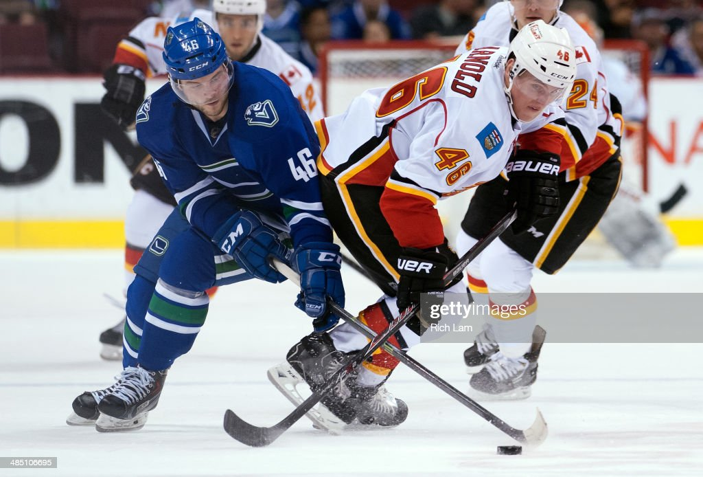 Bill Arnold #46 of the Calgary Flames and Nicklas Jensen #46 of the Vancouver Canucks battle for the puck during NHL action against the Vancouver Canucks on April 13, 2014 at Rogers Arena in Vancouver, British Columbia, Canada.