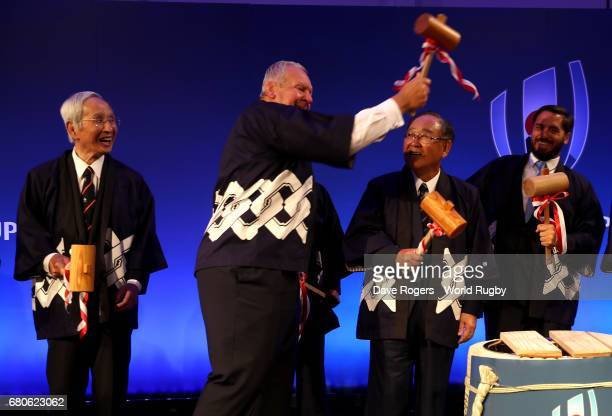 Bill Beaumont chairman of World Rugby jokingly pretends to hit World Rugby vice chairman Agustin Pichot with a wooden hammer watched by Fujito...