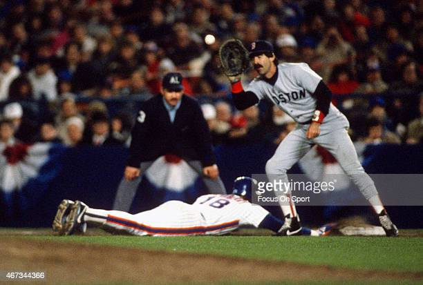 Bill Buckner of the Boston Red Sox takes the throw over to first base as Darryl Strawberry of the New York Mets dives in back safe during the 1986...