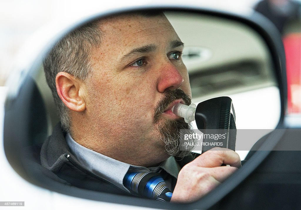 Bill Chastain State Director with LifeSafer is seen in the mirror of his car as he demonstrates a breath alcohol ignition interlock device during a...