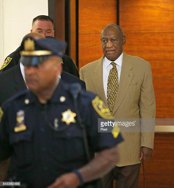 Bill Cosby right walks off the elevator to the second floor of the Montgomery County Courthouse on his way to Courtroom A surrounded by Montgomery...