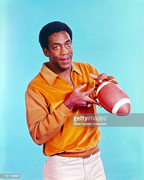 Bill Cosby US comedian and actor poses with an American football in a publicity portrait issued for the US television series 'I Spy' USA circa 1966...