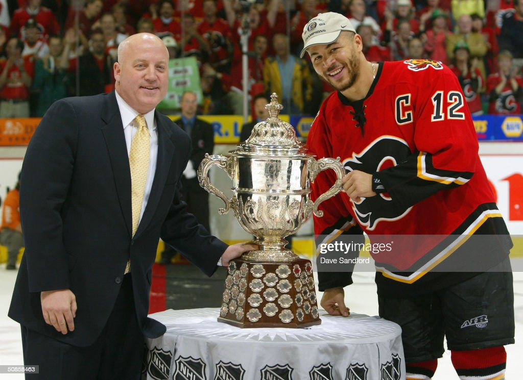 Bill Daly, Executive Vice President Chief Legal Officer of the NHL and Jarome Iginla #12 of the Calgary Flames pose with the 'Clarence Campbell' trophy after the Flames defeated the San Jose Sharks 3-1 in Game six of the 2004 NHL Western Conference Finals on May 19, 2004 at the Pengrowth Saddledome in Calgary, Alberta.