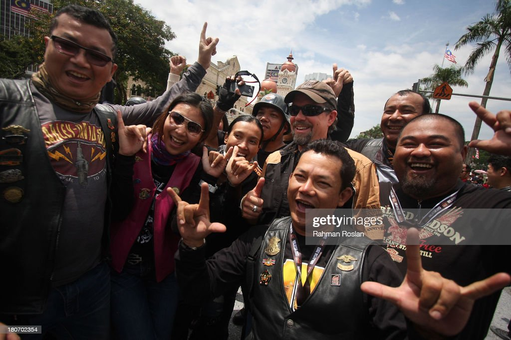 Bill Davidson (C) poses with fans during the bike parade in the heart of the city on September 16, 2013 in Kuala Lumpur, Malaysia. Malaysia hosts Asia Harley Days, a first of its kind event in Southeast Asia to engage with not only its consumers, but also with their fans in the region.