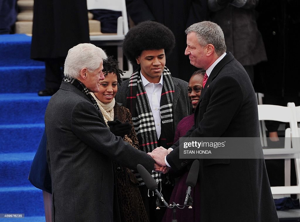 Bill de Blasio (R) after being sworn in as New York City Mayor by former US President Bill Clinton (L) shakes hands on the steps of City Hall in Lower Manhattan January 1, 2014 in New York. With them are de Blasio's daughter Chiara (2nd L), wife Chirlane (2nd R) and son Dante (C). AFP PHOTO/Stan HONDA