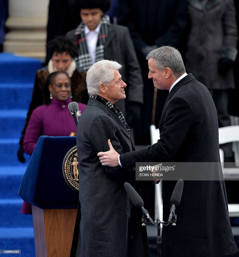 Bill de Blasio (R) just before being sworn in as New York City Mayor shakes hands with former US President Bill Clinton (L) on the steps of City Hall in Lower Manhattan January 1, 2014 in New York. Joining them are de Blasio's wife Chirlane (L, rear), daughter Chiara and son Dante. AFP PHOTO/Stan HONDA