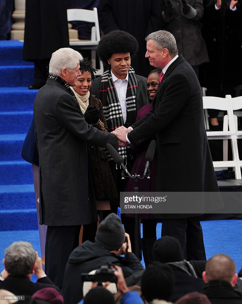 Bill de Blasio (R) reacts after being sworn in as New York City Mayor by former US President Bill Clinton (L) shakes hands on the steps of City Hall in Lower Manhattan January 1, 2014 in New York. With them are de Blasio's daughter Chiara (2nd L), wife Chirlane (2nd R) and son Dante (C). AFP PHOTO/Stan HONDA