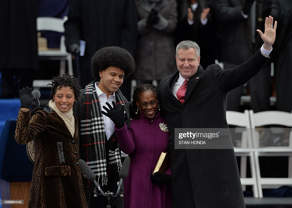 Bill de Blasio (R) waves after being sworn in as New York City Mayor on the steps of City Hall in Lower Manhattan January 1, 2014 in New York with his wife Chirlane (2nd R) and son Dante (2nd L) and daughter Chiara (L). AFP PHOTO/Stan HONDA