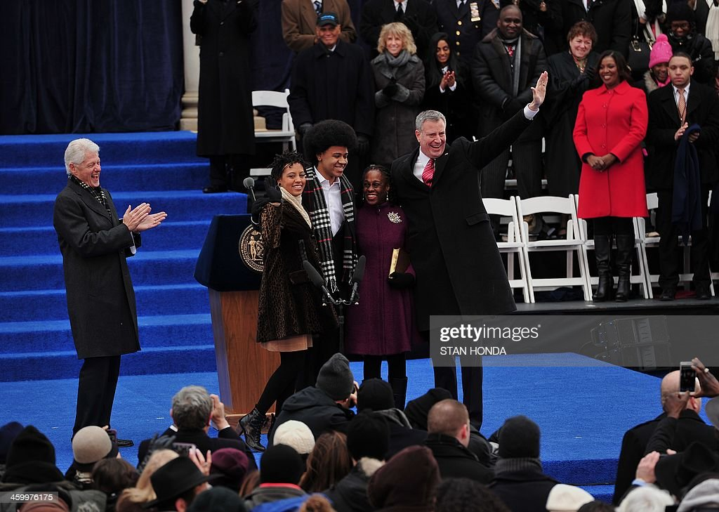 Bill de Blasio (R) waves after being sworn in as New York City Mayor on the steps of City Hall in Lower Manhattan January 1, 2014 in New York with his wife Chirlane (2nd R) and son Dante (2nd L) and daughter Chiara (L) as former US President Bill Clinton (far L) applaudes. AFP PHOTO/Stan HONDA