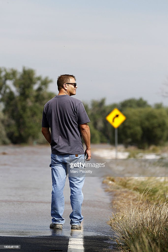 Bill Dinis of Wiggins, Colorado walks up to the edge of flood waters from the South Platte River as it washes over Morgan County Road 1 September 14, 2013 near Wiggins, Colorado. Heavy rains for the better part of week fueled widespread flooding in numerous Colorado towns. The historic flooding forced thousands to evacuate the area and more rain is predicted through the weekend.