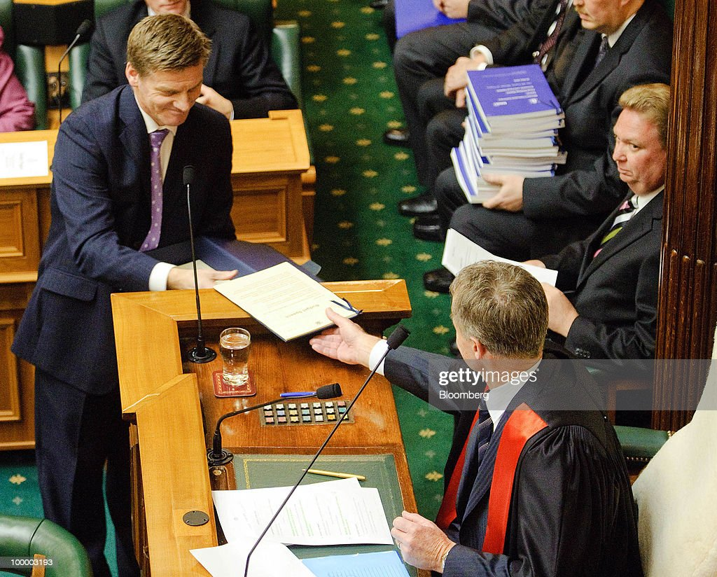 Bill English, New Zealand's finance minister, left, passes a copy of the budget to Lockwood Smith, speaker of the House of Representatives in Parliament, in Wellington, New Zealand, on Thursday, May 20, 2009. New Zealand will raise sales tax for the first time in two decades and lower income taxes to encourage household saving, aiming to reduce the economy's 'vulnerability' to concerns about sovereign debt. Photographer: Mark Coote/Bloomberg via Getty Images