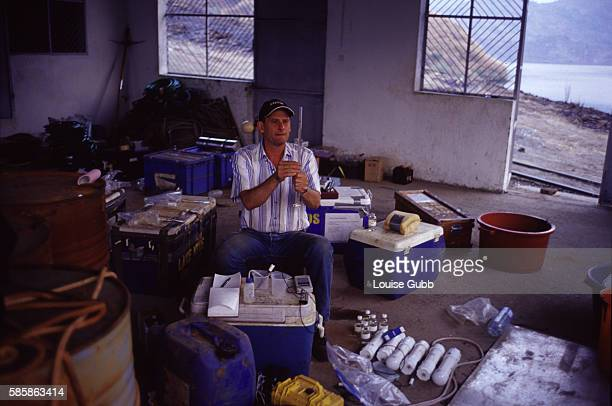 Bill Evans of the US Geological Service takes measurements from water samples from Lake Nyos using the storage shed as a makeshift laboratory He and...