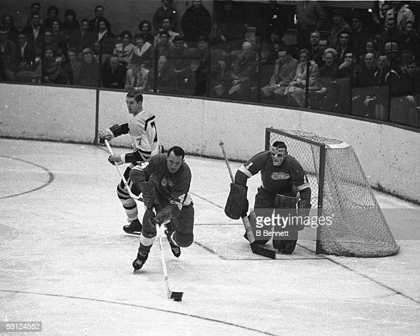 Bill Gadsby of the Detroit Red Wings skates with the puck as his teammate goalie Terry Sawchuk looks on during their game against the Boston Bruins...