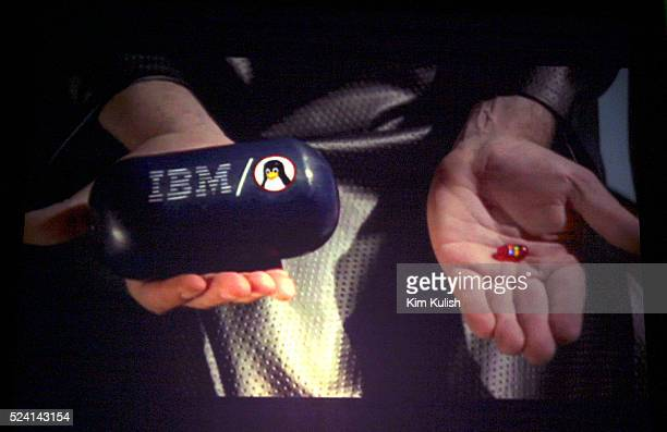Bill Gates Chairman and Chief Software Architect of Microsoft holds a large 'blue pill' with the IBM logo on it and a small 'red pill' with the...