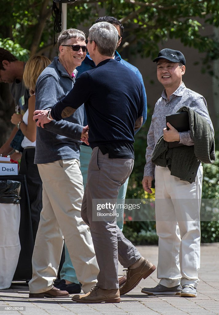 Bill Gates chairman and founder of Microsoft Corp left shakes hands with Tim Cook chief executive officer of Apple Inc center as Masayoshi Son...