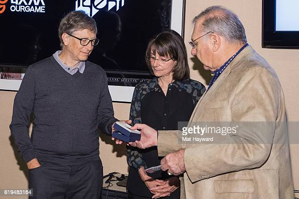Bill Gates is presented with a medal by Al Levy of the American Congtract Bridge League while Bridge player Sharon Osberg watches before the first...