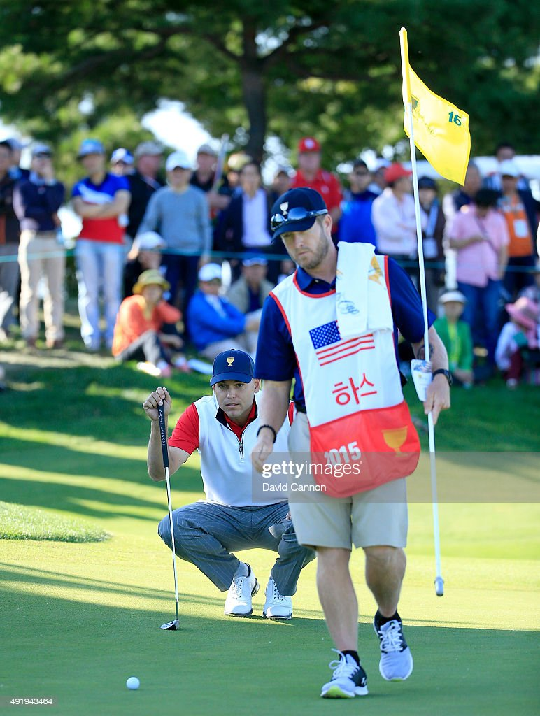 Bill Haas of the United States team lines up a birdie putt with his caddie John Wood on the 16th green in his match with Chris Kirk against Thongchai Jaidee and Charl Schwartzel of the International Team during the Friday four-ball matches at The Presidents Cup at Jack Nicklaus Golf Club Korea on October 9, 2015 in Songdo IBD, Incheon City, South Korea