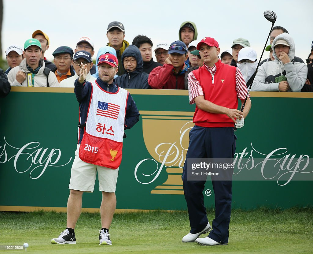 Bill Haas of the United States Team lines up his tee shot on the 18th hole with his caddie John Wood during the Sunday singles matches at The...