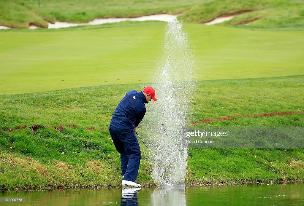 Bill Haas of the United States team plays his second shot at the 11th hole from the water hazard in his match against Sangmoon Bae of South Korea and...