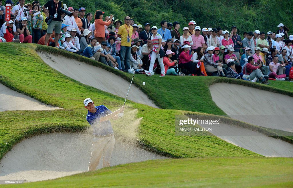 Bill Haas of the US (bottom L) plays from the bunker at the 15th hole during the WGC-HSBC Champions tournament held on the Olazabal Course at the Mission Hill Golf Club in Dongguan on November 4, 2012. Els finished on 19 under par. AFP PHOTO/Mark RALSTON