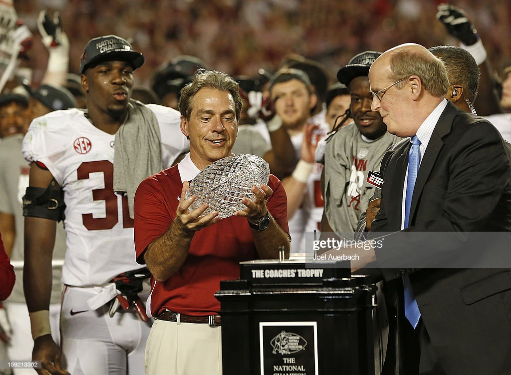 Bill Hancock, BCS executive director, looks on as head coach Nick Saban of the Alabama Crimson Tide lifts the Coaches' Trophy after defeating the Notre Dame Fighting Irish during the 2013 Discover BCS National Championship Game at Sun Life Stadium on January 7, 2013 in Miami Gardens, Florida. Alabama defeated Notre Dame 42-14.