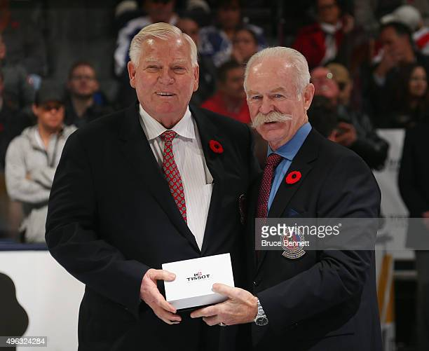 Bill Hay receives his Hockey Hall of Fame blazer from the Chairman of the Hockey Hall of Fame Lanny McDonald prior to the Legends Classic game on...