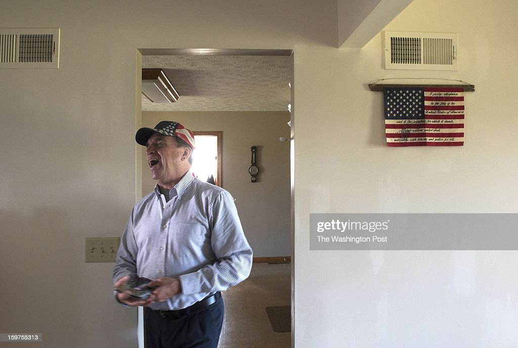 Bill Herr laughs after finding a photograph taken of him during fourth of July festivities. Herr served in the military and displays his patriotism with flags -- he is wearing a flag cap and has flags throughout his home. The flag on the wall was purchased by his wife, Sally, when Bill was serving in Iraq.