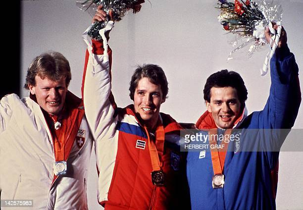 Bill Johnson of the US flanked by Peter Müller from Switzerland and Anton Steiner from Austria smiles on the podium of the men's downhill 16 February...