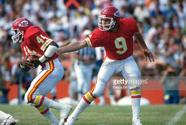 Bill Kenney of the Kansas City Chiefs hands the ball off to Herman Heard against the Miami Dolphins during an NFL football game September 22 1985 at...