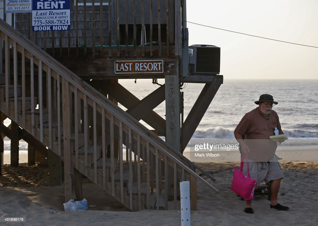 Bill Kirk of Ashland Ky. carries his belongings from the beach house he rented, before complying with the mandatory evacuation orders for Hatteras Island, July 3, 2014 in Rodanthe, North Carolina. A Hurricane warning has been issued for North Carolina's Outer Banks due to approaching Tropical Storm Arthur that is expected to gain strength and become a category 1 hurricane before it passes the area.