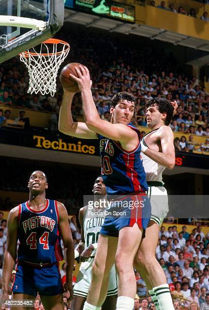 Bill Laimbeer of the Detroit Pistons grabs a rebound in front of Kevin McHale of the Boston Celtics during an NBA basketball game circa 1985 at the...