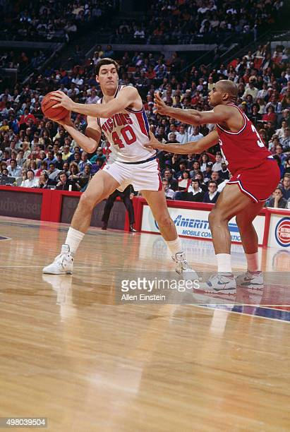 Bill Laimbeer of the Detroit Pistons passes the ball against Charles Barkley of the Philadelphia 76ers circa 1990 at the Palace of Auburn Hills in...