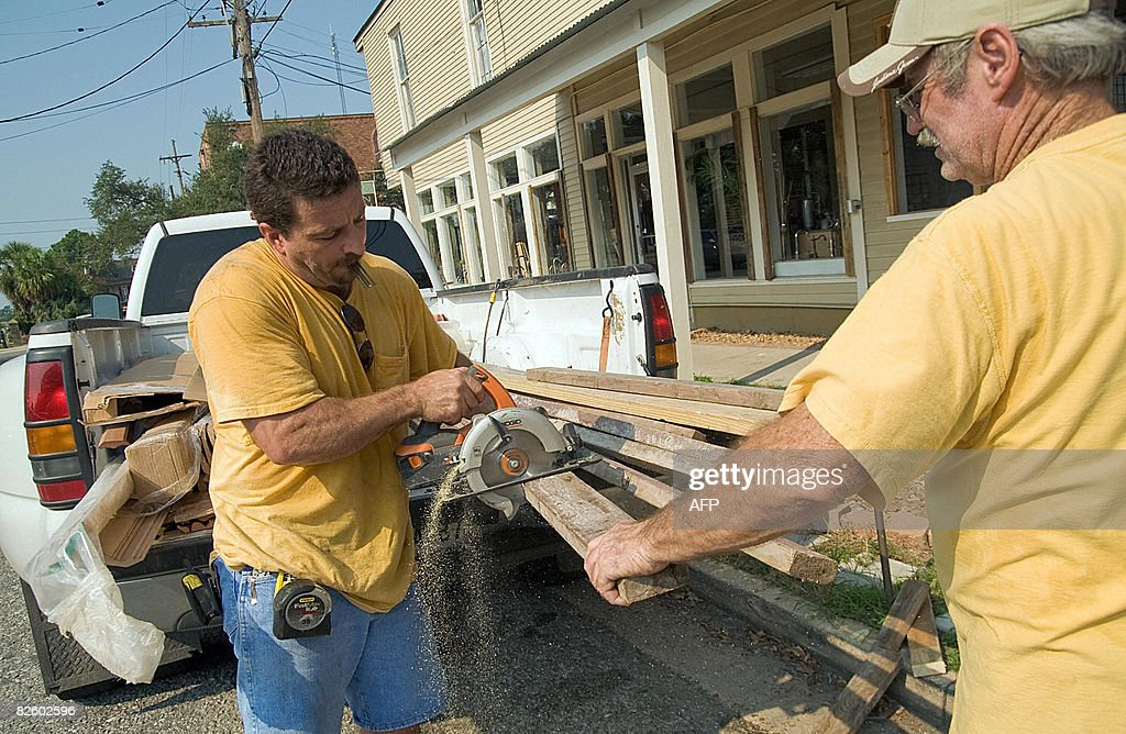 Bill Lister Holds A Support For Window Covering While Tyler Malejko Saws At The  Kitchen Connection