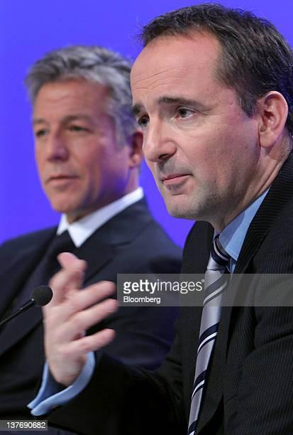Bill McDermott cochief executive officer of SAP AG left listens as Jim Hagemann Snabe cochief executive officer of SAP AG gestures during a news...