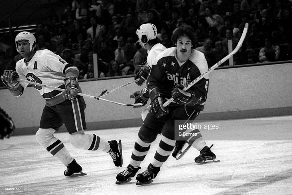 Bill Mikkelson of the Washington Capitals and Garry Howatt of the New York Islanders skate on the ice on Febuary 8 1975 at the Nassau Coliseum in...