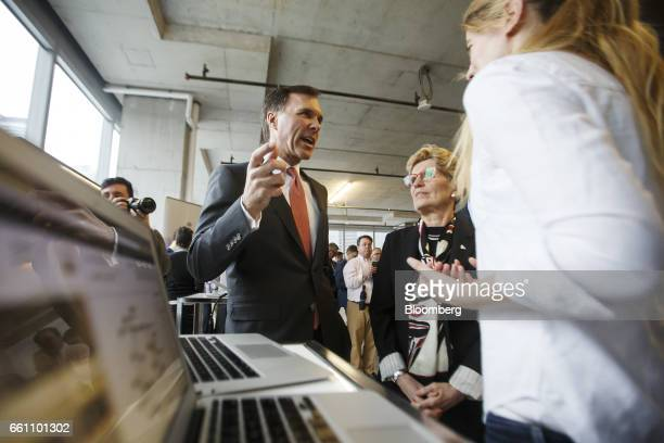 Bill Morneau Canada's finance minister center left speaks as Kathleen Wynne premier of Ontario center right looks on during a demonstration at the...