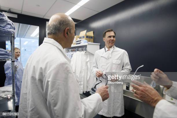 Bill Morneau Canada's finance minister right and Reza Moridi minister of research and innovation of Ontario second left put on lab coats and...