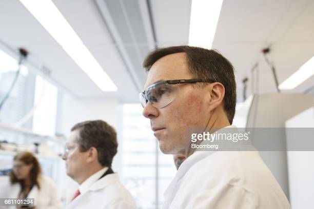 Bill Morneau Canada's finance minister right observes while wearing a lab coat and protective goggles during a tour of the Centre for...