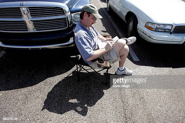 Bill Morris does a crossword puzzle as he waits in line for FEMA supplies that were hours late in arrving after Hurricane Wilma struck the area...