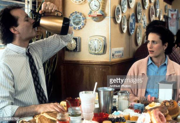 Bill Murray puts down a pitcher of coffee with Andie MacDowell in a scene from the film 'Groundhog Day' 1993