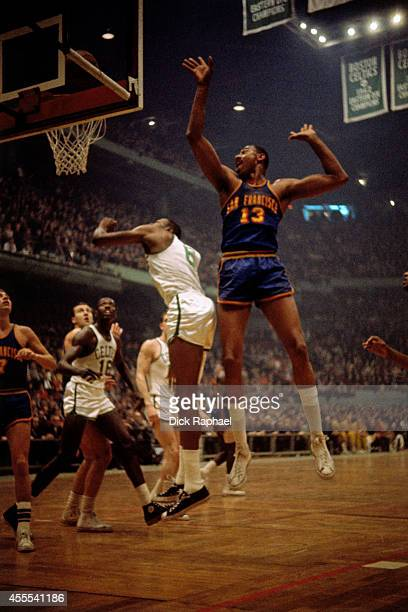 Bill Russell of the Boston Celtics shoots the ball against Wilt Chamberlain of the San Francisco Warriors during a game circa 1964 at the Boston...