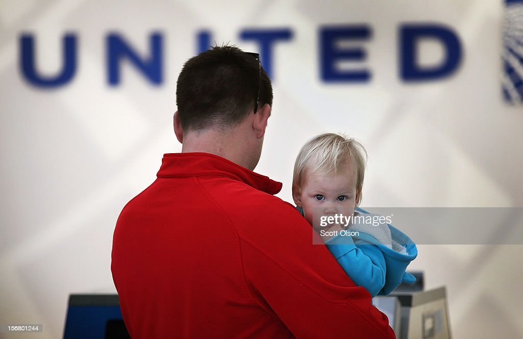 Bill Sanford holds his 14-month-old daughter Clare as he checks in for a flight at O'Hare International Airport on November 21, 2012 in Chicago, Illinois. The two were flying to New Jersey to spend the Thanksgiving holiday with family. The Chicago Department of Aviation anticipates nearly 1.8 million passengers will travel through Chicago's two airports for the Thanksgiving holiday travel period between Tuesday, November 20 and Tuesday November 27.