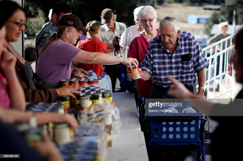 Bill ShawMiddle receives donated food items from volunteer Chris Lashmet at a Feeding America truck on Thursday November 3 2011 at the Descanso Town...