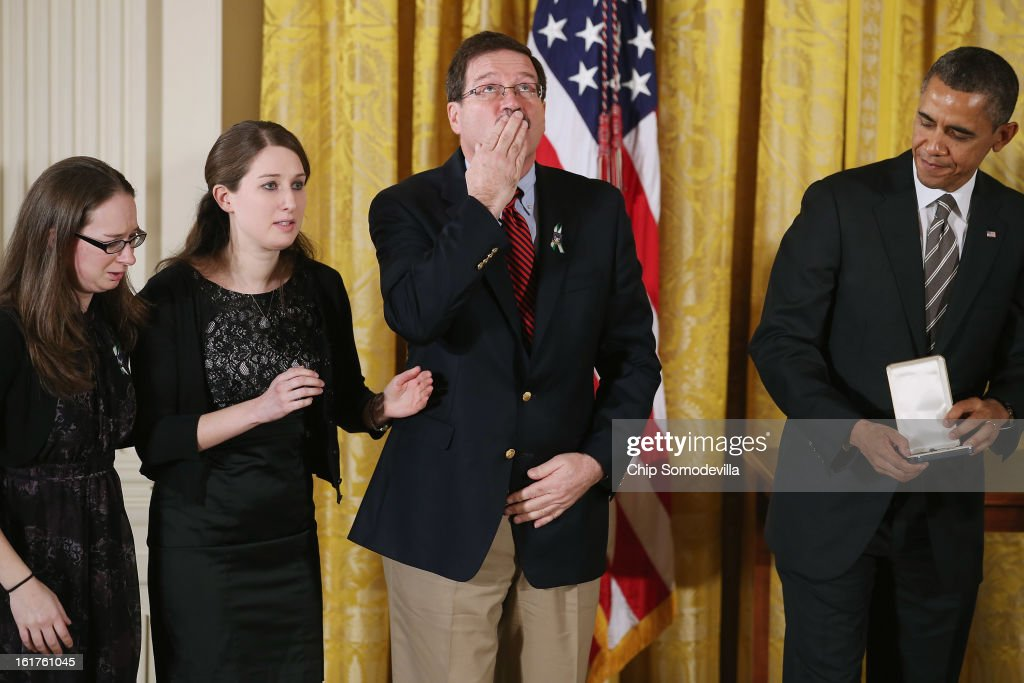 Bill Sherlach blows a kiss skyward as U.S. President Barack Obama presents him and daughters Katy Sherlach and Maura Lynn Schwartz with the 2012 Presidential Citizens Medal, the nation's second-highest civilian honor, on behalf of their wife and mother Mary Sherlach in the East Room of the White House February 15, 2013 in Washington, DC. School psychologist Mary Sherlach was killed during a mass shooting that left 26 people dead at Sandy Hook Elementary School in December 2012. 'Their selflessness and courage inspire us all to look for opportunities to better serve our communities and our country,' Obama said about this year's recepients.