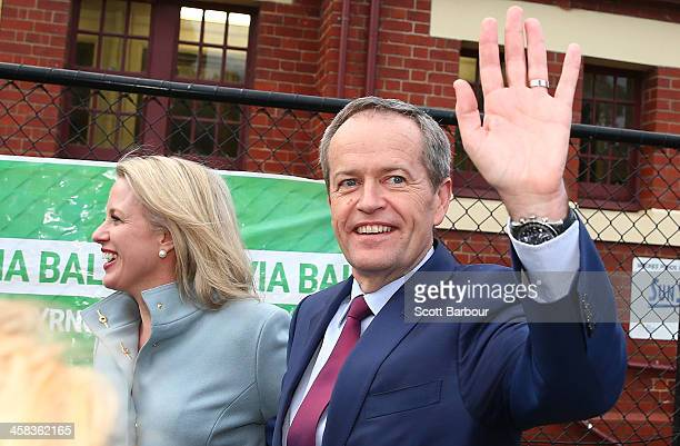 Bill Shorten Leader of the Opposition and Leader of the Australian Labor Party waves as he walks with his wife Chloe Bryce past election posters...