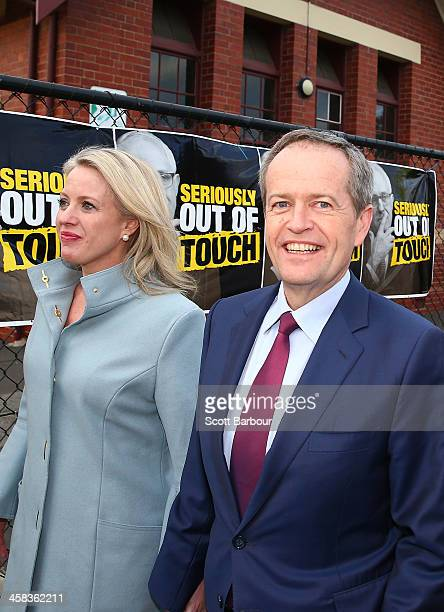 Bill Shorten Leader of the Opposition and Leader of the Australian Labor Party and his wife Chloe Bryce walk past election posters featuring current...