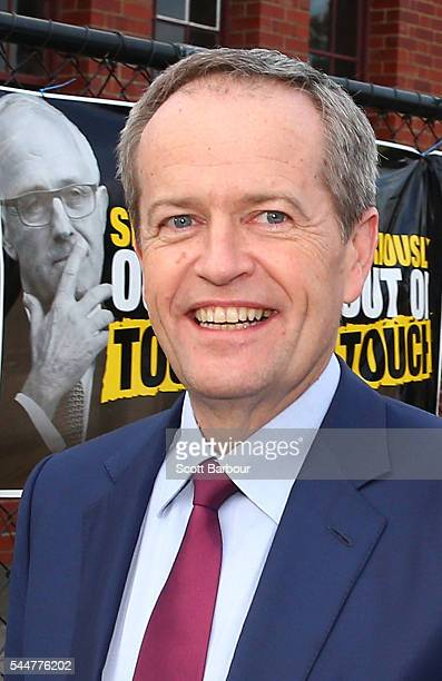 Bill Shorten Leader of the Opposition and Leader of the Australian Labor Party walks past election posters featuring current Australian Prime...