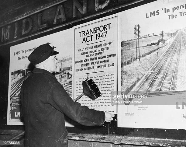 Bill sticker putting up a poster 30 December 1947 'This nationalisation poster giving notice of the passing of control of the railways to the British...